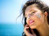 image of suntanning  - Suntan Lotion Woman Applying Sunscreen Solar Cream - JPG