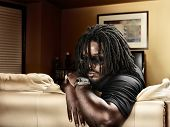 picture of dreads  - cool black man with dreads on leather couch - JPG