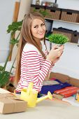 Lifestyle. Cute, attractive woman with grass in pot