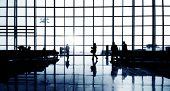 Silhouettes Of Multi-Ethnic Group Of Business People Waiting In An Airport Terminal