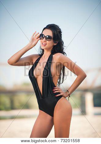 Portrait of young sexy brunette girl in black low-cut swimsuit posing on a beach with a bridge