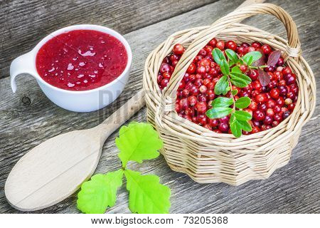 Fresh cranberries with cranberrys jam near on wooden table