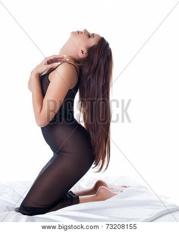 Side view of excited slim model in erotic negligee