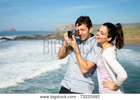 Young Couple Taking Photo To The Sea