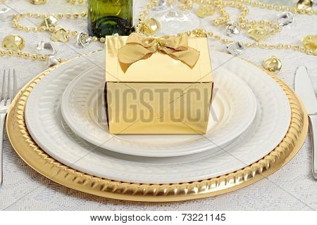 closeup gold gift with table setting