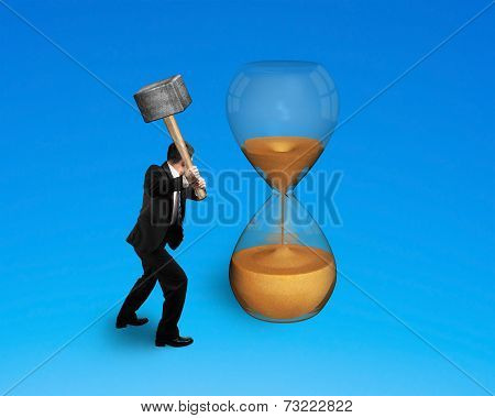 Male Hand Holding Hammer To Hit Hourglass