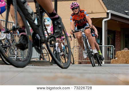 Low-angle Perspective Of Female Cyclists Racing Into Turn