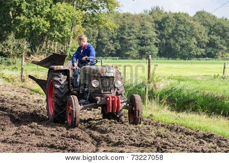 Farmer Riding With An Old Tractor During A Dutch Agricultural Festival