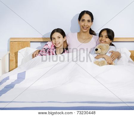 Hispanic mother and daughters sitting in bed
