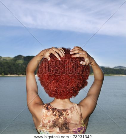 Rear view of Hispanic woman wearing wig