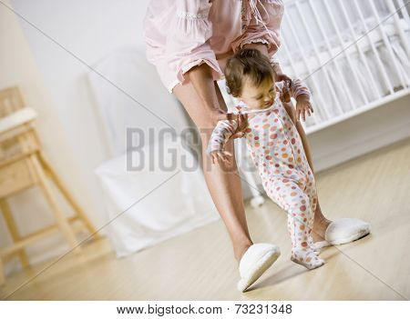Hispanic mother helping baby walk