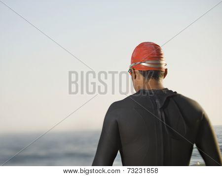 Rear view of Hispanic man wearing wetsuit