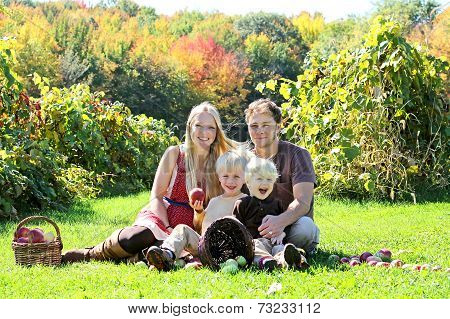 Happy Family Of Four Having Fruit Snack At Autumn Apple Orchard