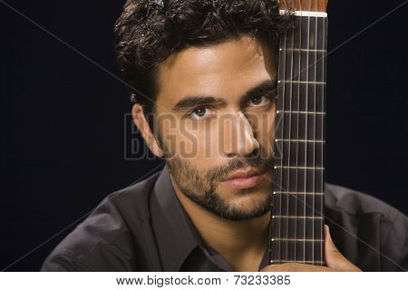 Hispanic man holding acoustic guitar