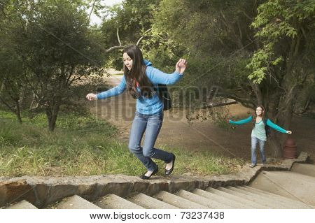 Hispanic teenaged girls walking up stone steps