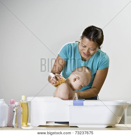Asian mother bathing baby