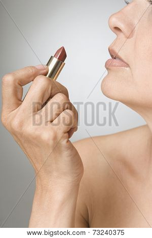 Hispanic woman holding lipstick