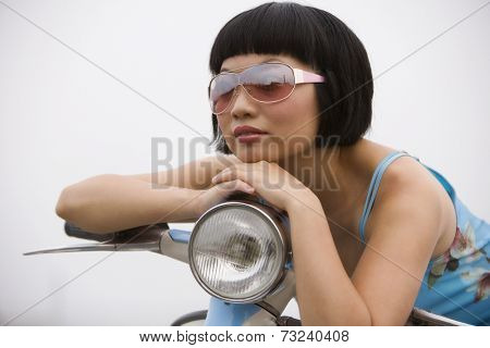 Asian woman sitting on motor scooter