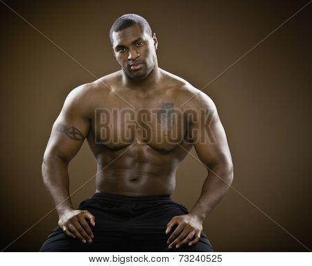 Bare-chested African man with hands on thighs