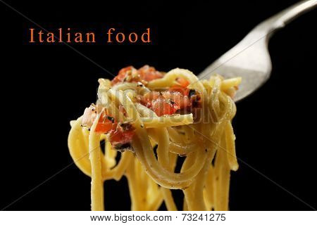 Italian pasta spaghetti on fork on black background