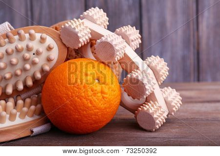 Roller brush, orange and oval brushes on wooden table in front of a wooden wall