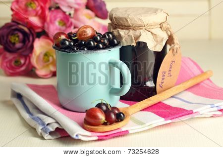 Ripe blackcurrants in mug and glass jar with tasty jam on light wooden background.