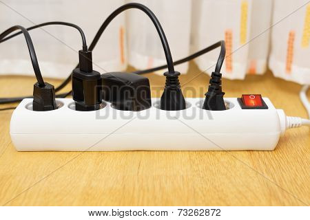 Many Electrical Appliances Pluged In Surge Protector. Power Consuption Concept