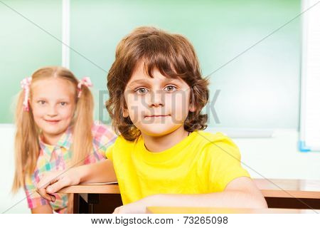 Boy and girl looking straight sitting at desks