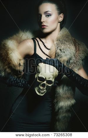 Attractive young lady with the scull over the smoky background