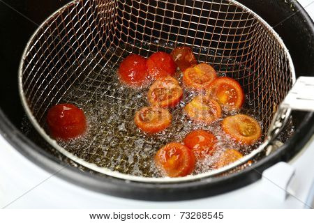 Tomato in deep fryer, closeup
