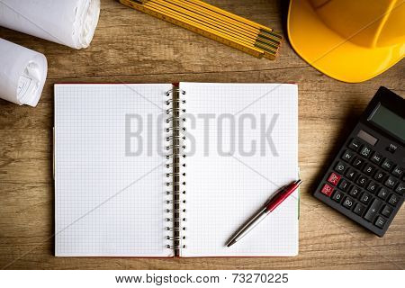 wooden desk with open notebook, blueprint rolled, hamlet, calculator