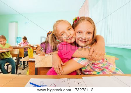 Happy girls in a cuddle sitting together at desk