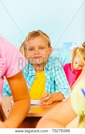 Blond boy looks straight and sit with other pupils
