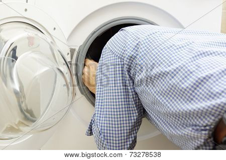 Handyman Repairing A Washing Machine