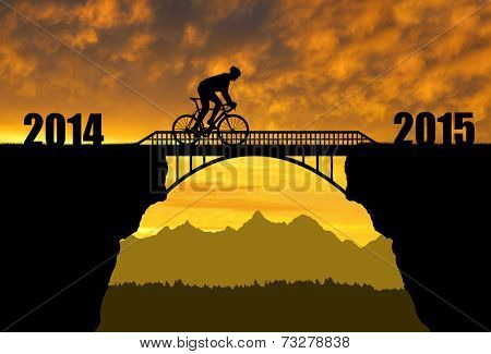 Cyclist riding across the bridge at sunset .Forward to the New Year 2015