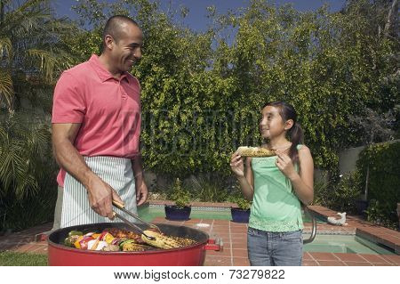 Hispanic father and daughter barbequing