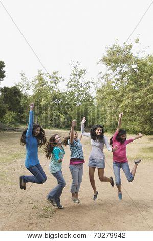 Hispanic teenaged girls cheering and jumping