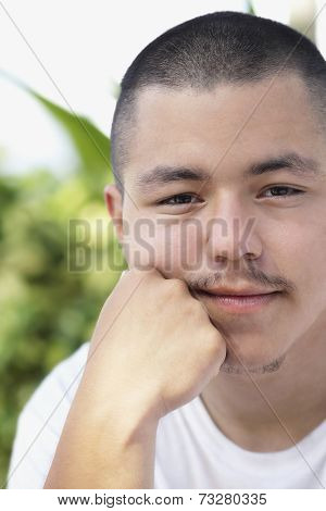 Pacific Islander man resting chin on hand