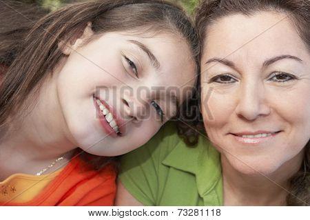 Hispanic girl leaning on mother's shoulder