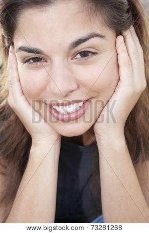 Hispanic woman resting chin on hands
