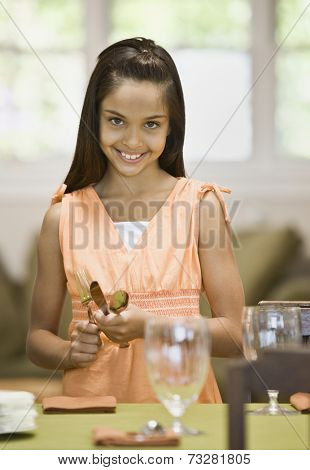 Hispanic girl setting table