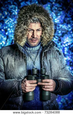 Handsome brutal man dressed in winter clothes covered with frost looking through binoculars.