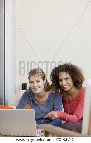 Multi-ethnic women next to laptop