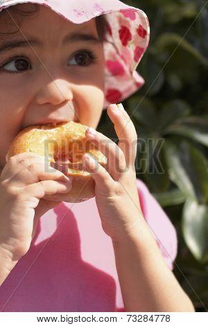 Hispanic baby girl eating doughnut