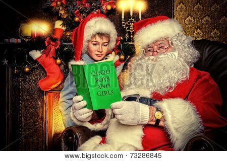 Santa Claus and a cute boy reading a list of good boys and girls. Christmas home d�?�©cor.