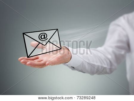Businessman holding a virtual envelope with at symbol concept for e-mail, global communications, mail or contact us
