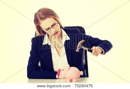 Beautiful business woman is trying to destroy piggy bank with hammer. Isolated on white.