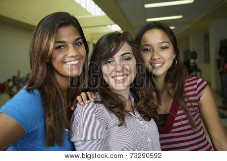Multi-ethnic teenaged girls hugging in school hallway
