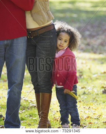 African girl hugging mother's legs