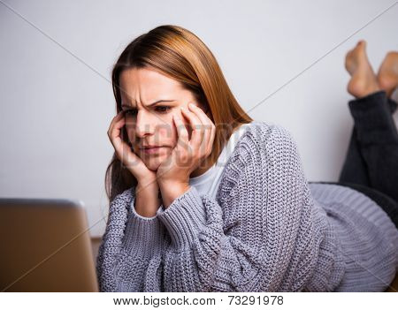 Young Woman Frowning While Looking At Laptop